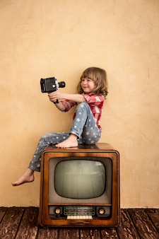 Bambino che gioca in casa. kid prendendo selfie con fotocamera retrò. concetto di cinema