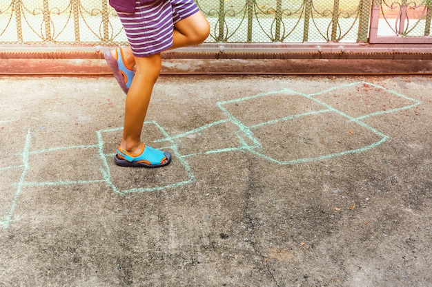 Bambino che gioca il gioco di campane sul pavimento di calcestruzzo all'aperto