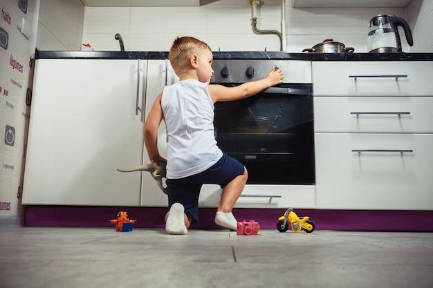 Bambino che gioca in cucina con una stufa a gas.