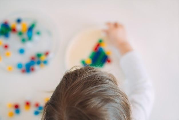 Bambino che gioca a mosaico sul tavolo a casa con sfocatura.