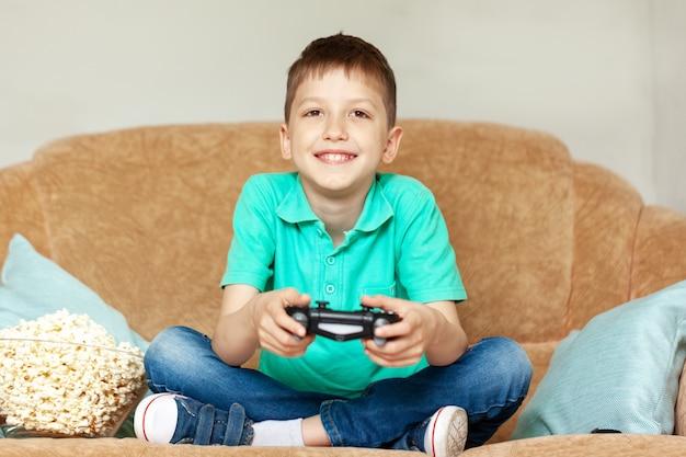Bambino giocare ai videogiochi online e mangiare popcorn seduto sul divano nel salotto di casa.