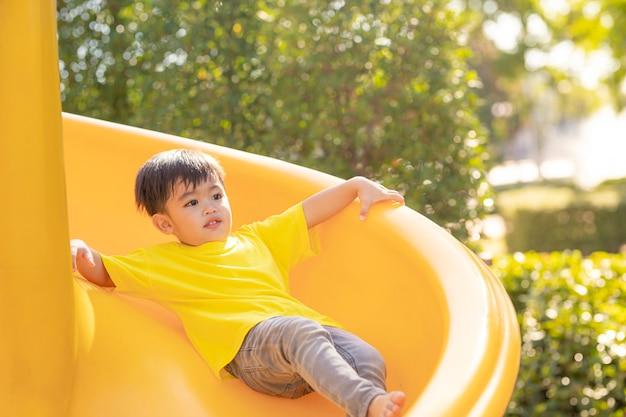 Bambino che gioca nel parco giochi all'aperto. i bambini giocano a scuola o nel cortile dell'asilo. bambino attivo su scivolo colorato e altalena. attività estive salutari per bambini.