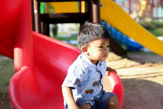 Bambino che gioca nel parco giochi all'aperto.