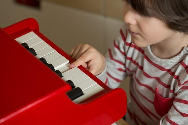 Bambino che suona il pianoforte giocattolo