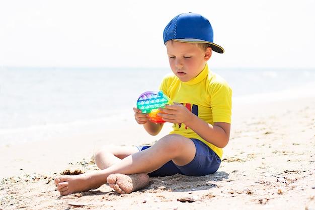 Bambino che gioca con il fidget pop it on the beachnuovo giocattolo sensoriale per bambini e adultivista dall'alto