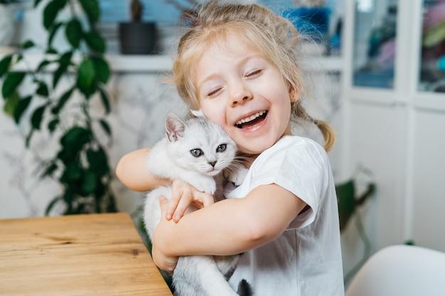 Bambino che gioca con il piccolo gatto. la bambina tiene un gattino bianco.