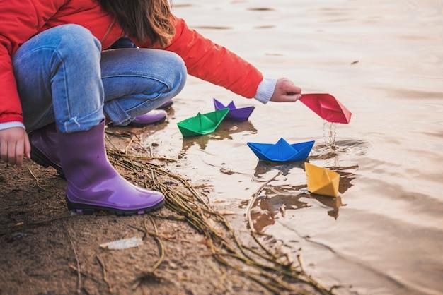 Bambino che gioca con barchette di carta in acqua di sorgente.lago o fiume.