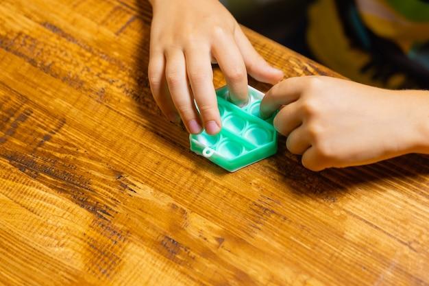 Bambino che gioca con il pop premendo le bolle con la vista dall'alto del ditonuovo giocattolo antistress per bambini...