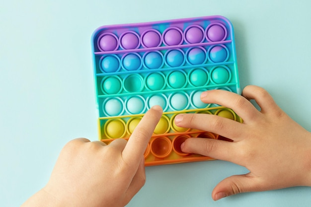 Bambino che gioca con il pop arcobaleno che preme le bolle con la vista del dito