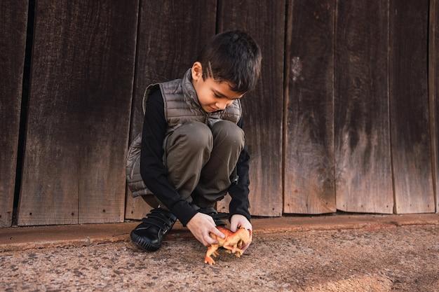 Bambino che gioca con un dinosauro giocattolo all'aperto.