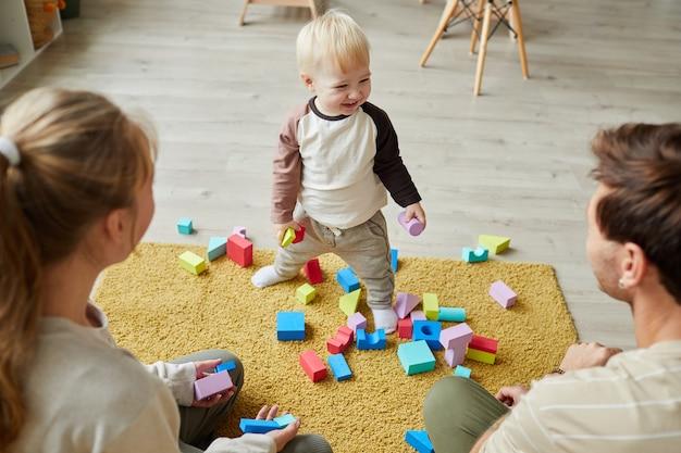Bambino che gioca con i giocattoli sul pavimento insieme ai suoi genitori a casa