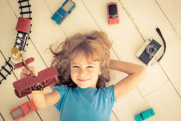 Bambino che gioca con i giocattoli vintage a casa. girl power e concetto di femminismo