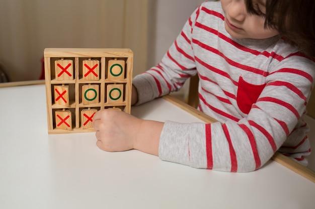 Bambino che gioca con tris in legno