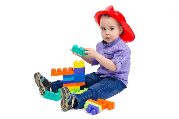 Il bambino gioca al costruttore con il costruttore seduto sul pavimento