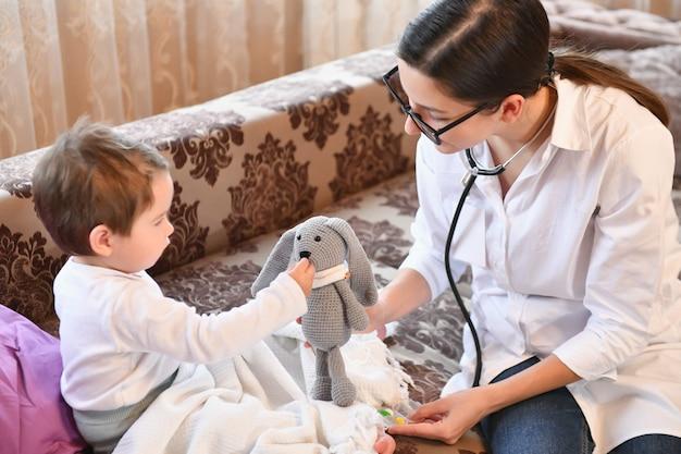 Il bambino gioca al dottore con un dottore. medico di famiglia