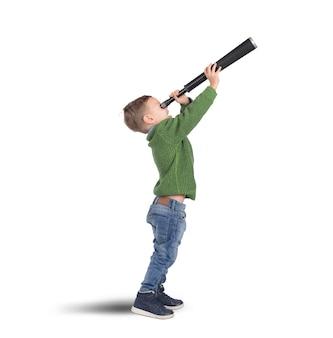 Il bambino gioca ad esplorare e scoprire con il binocolo