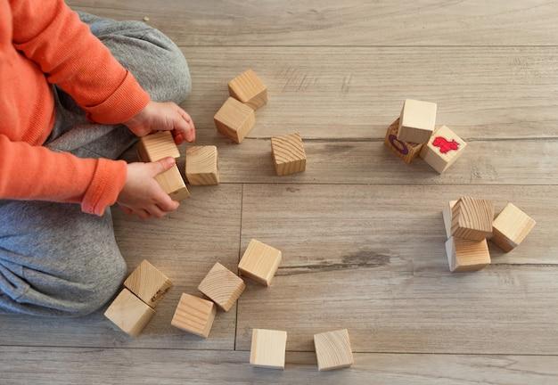 Un bambino gioca in casa sul pavimento con cubetti di legno. la vista dall'alto.