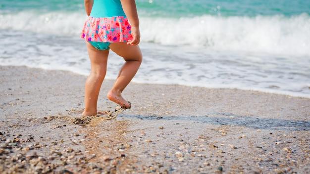 Il bambino gioca e spruzza nel mare
