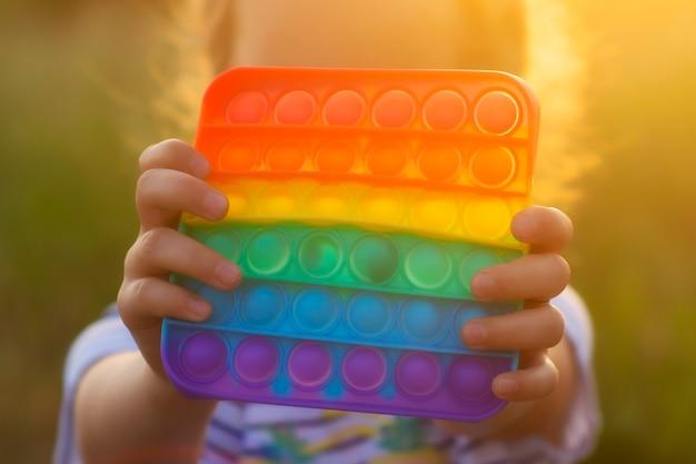 Il bambino gioca con un colorato gioco arcobaleno di poppit. primo piano di fidget in silicone.