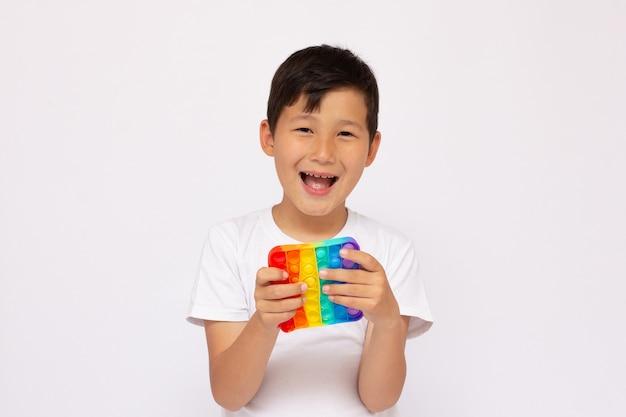 Il bambino gioca con il gioco di fidget sensoriale pop-it