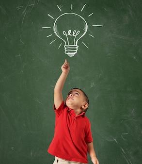 Il bambino indica una lampadina disegnata sopra la sua testa sulla lavagna