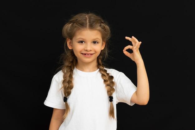 Un bambino si pone su uno sfondo nero.