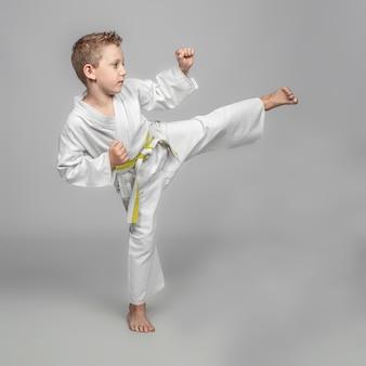 Bambino che pratica il karate in posizione di calcio. girato in studio.