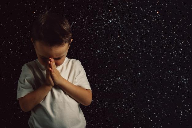Un bambino prega dio con le mani a filo