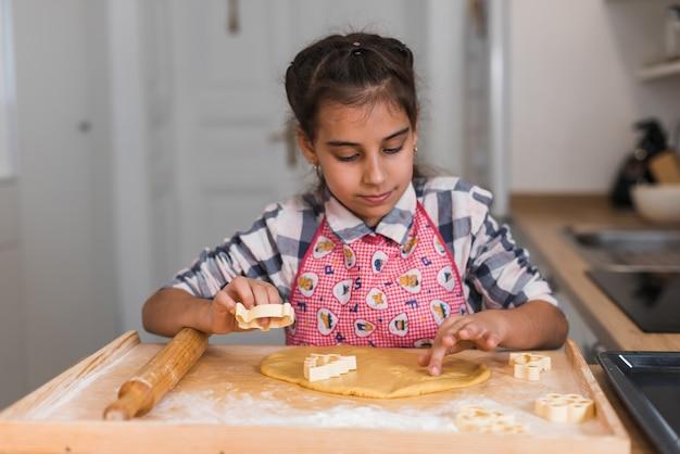 Il bambino prepara i biscotti e ritaglia delle figurine di pasta arrotolata a forma di cuore. mani del bambino che producono i biscotti dalla pasta cruda sotto forma di cuore, primi piani.