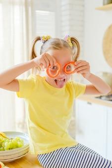Bambino che prepara cibo sano e si diverte tiene un peperone davanti agli occhi