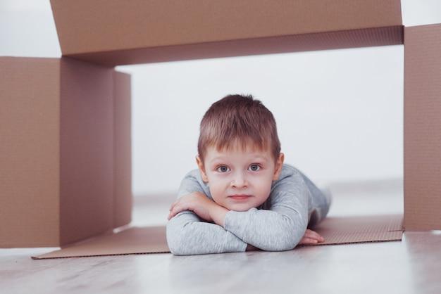 Ragazzo del bambino in età prescolare che gioca all'interno della scatola di carta. infanzia, riparazioni e nuovo concetto di casa.