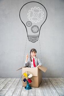 Il bambino finge di essere un uomo d'affari. bambino che gioca in casa. immaginazione, idea e concetto di successo