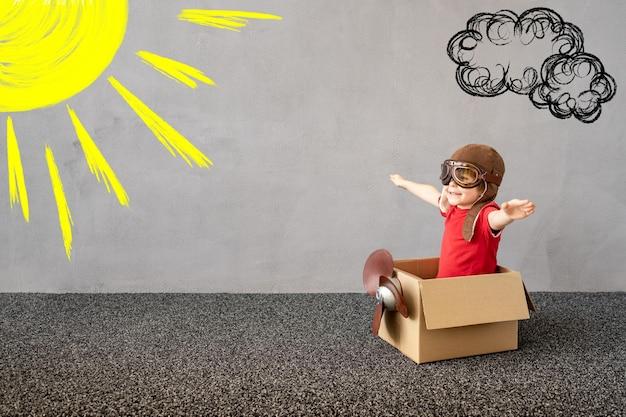 Il bambino finge di essere un pilota il bambino si diverte a casa l'immaginazione dei bambini