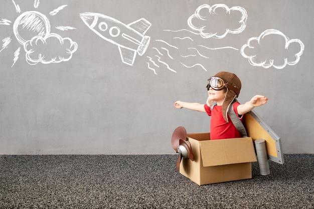 Bambino finge di essere pilota bambino che si diverte a casa bambino felice che sogna di viaggiare