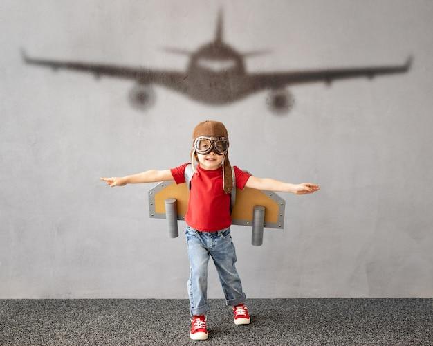 Il bambino finge di essere un pilota. bambino che si diverte a casa. vacanze estive e concetto di viaggio