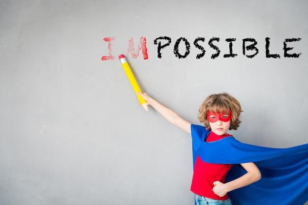 Il bambino finge di essere un supereroe super eroe bambino che cancella testo impossibile creatività e concetto di vincitore winner