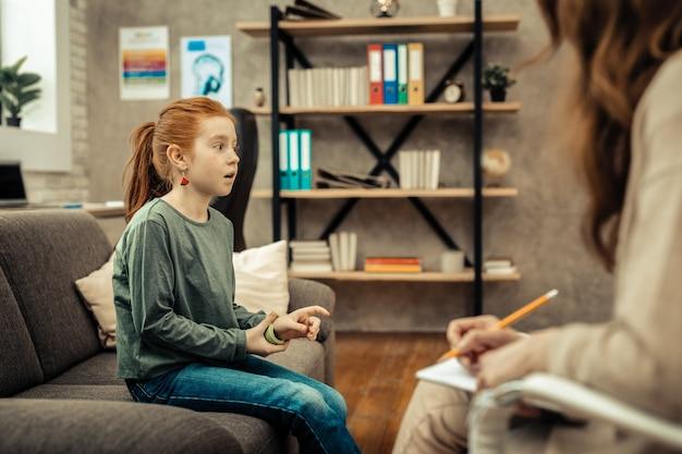 Problemi del bambino. carina ragazza dai capelli rossi seduta sul divano mentre racconta i suoi problemi