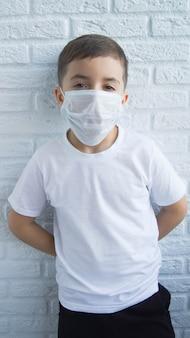 Bambino in una maschera protettiva sul bianco