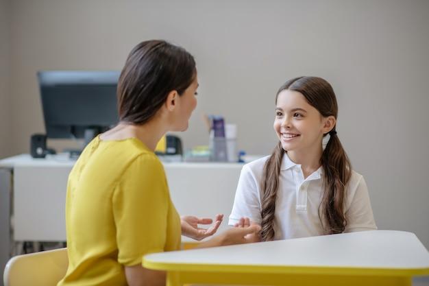 Psicologo infantile seduto con le spalle alla telecamera dando sessione individuale con ragazza dai capelli scuri carina seduta di fronte