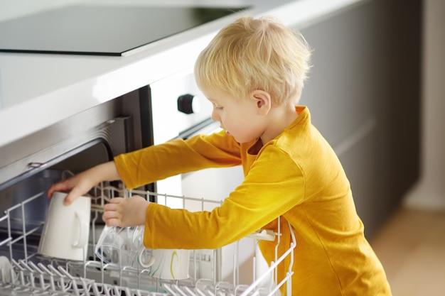 Il bambino mette le stoviglie sporche nella lavastoviglie di casa. avvicinamento.