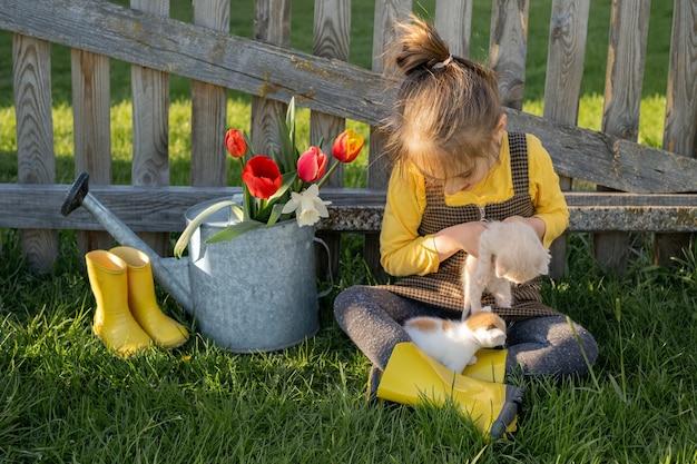 Un bambino con stivali da pioggia e abiti da campagna siede vicino a un vecchio recinto di legno e un annaffiatoio con fiori primaverili