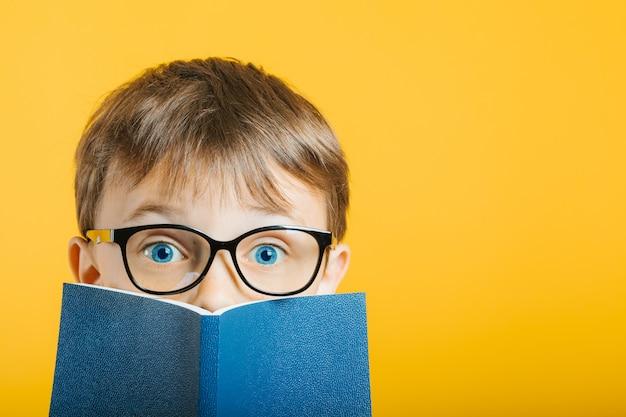 Il bambino legge un libro contro un muro luminoso