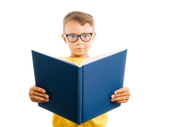 Il bambino legge un libro contro una parete luminosa
