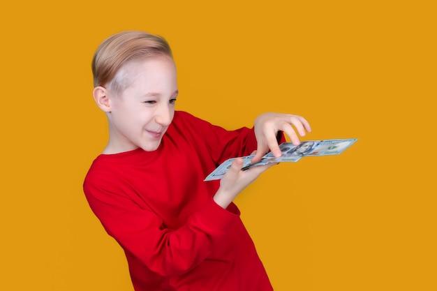 Un bambino in rosso tiene in mano banconote da un dollaro