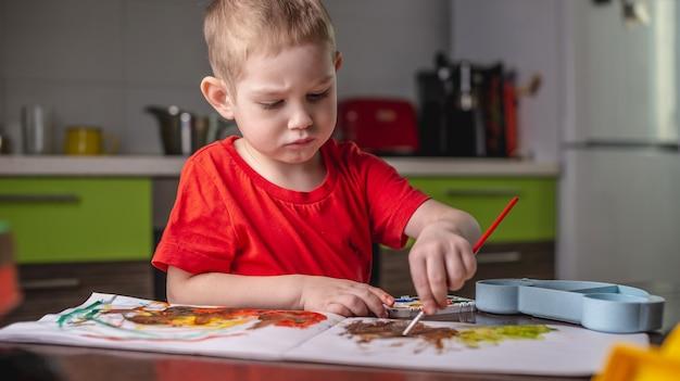 Un bambino con una maglietta rossa dipinge con acquerelli colorati al tavolo