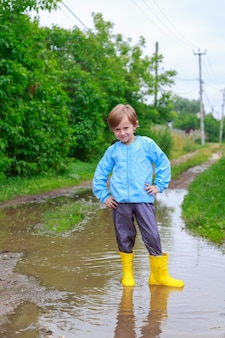 Bambino in stivali di gomma e impermeabile che gioca in una pozzanghera