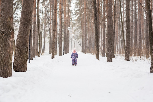 Bambino che corre nel bosco innevato