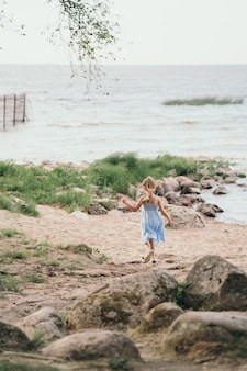 Il bambino corre lungo la riva del mare felice estate per un bambino foto verticale con un bambino che corre roccioso...