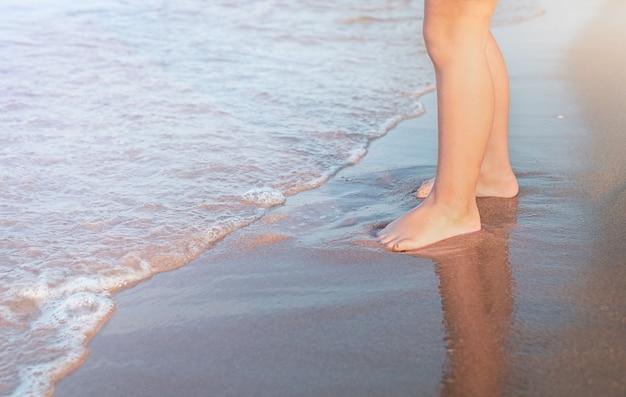 I piedi del bambino su una spiaggia sabbiosa