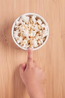 Il dito del bambino che indica la ciotola con popcorn su fondo di legno. home cinema per bambini